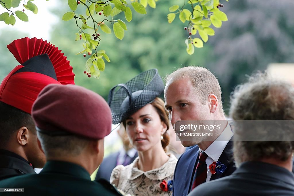 Britain's Prince William (R) and his wife Duchess Catherine of Cambridge (C) talk soldiers as they attend the memorial ceremony on July 1, 2016, at the Thiepval Memorial in Thiepval, during which Britain and France will mark the 100 years since soldiers emerged from their trenches to begin one of the bloodiest battles of World War I (WWI) at the River Somme. Under grey skies, unlike the clear sunny day that saw the biggest slaughter in British military history a century ago, the commemoration kicked off at the deep Lochnagar crater, created by the blast of mines placed under German positions two minutes before the attack began at 7:30 am on July 1, 1916. / AFP / POOL / Francois Mori
