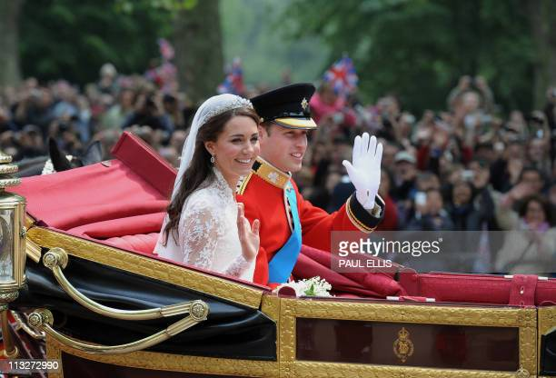 Britain's Prince William and his wife Kate Duchess of Cambridge wave as they travel in the 1902 State Landau carriage along the Processional Route to...