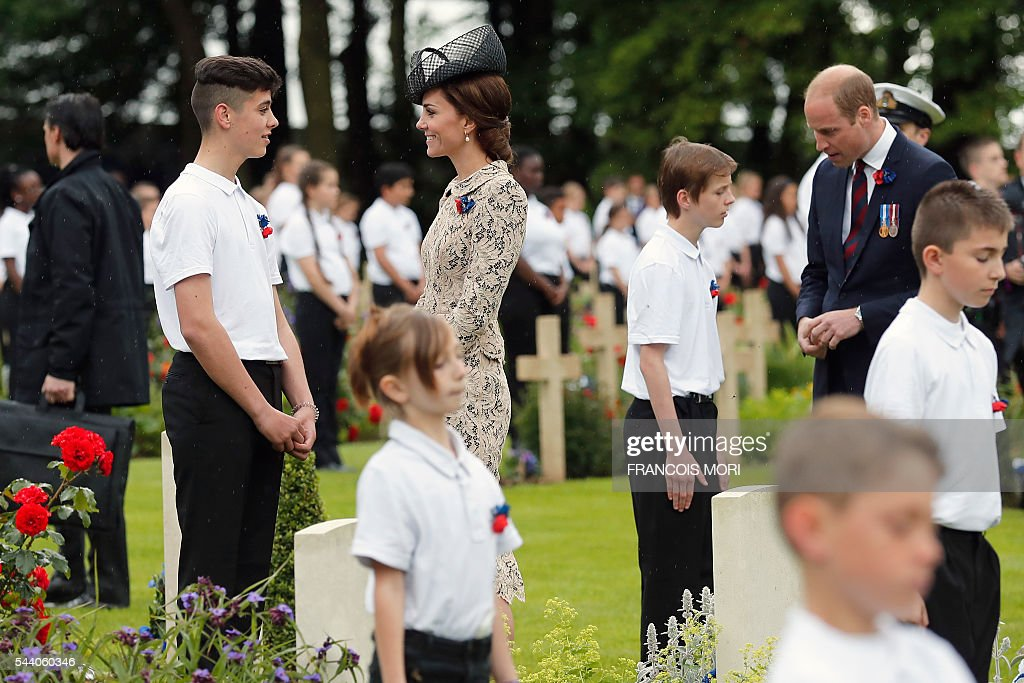 Britain's Prince William (R) and his wife the Duchess Catherine of Cambridge (C) talk with young volunteers in the cemetery of the Thiepval Memorial as they attend the memorial ceremony on July 1, 2016, in Thiepval, during which Britain and France will mark the 100 years since soldiers emerged from their trenches to begin one of the bloodiest battles of World War I (WWI) at the River Somme. Under grey skies, unlike the clear sunny day that saw the biggest slaughter in British military history a century ago, the commemoration kicked off at the deep Lochnagar crater, created by the blast of mines placed under German positions two minutes before the attack began at 7:30 am on July 1, 1916. / AFP / POOL / Francois Mori
