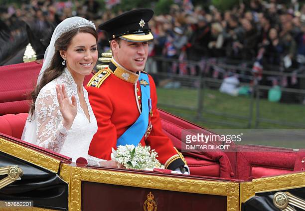 Britain's Prince William and wife Kate Duchess of Cambridge wave as they travel in the 1902 State Landau carriage along the Processional Route to...