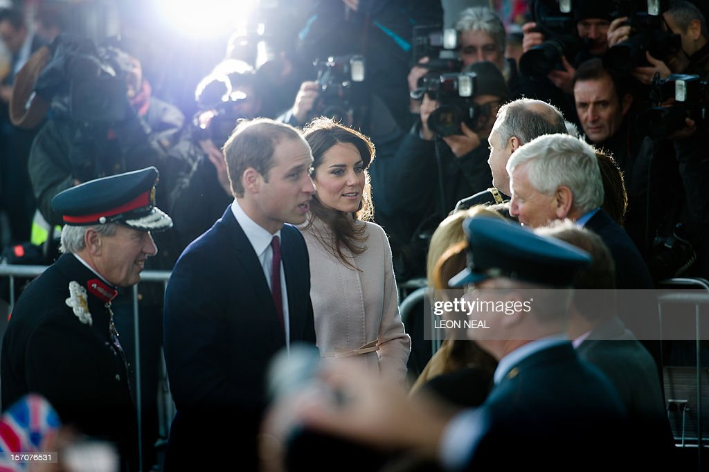 Britain's Prince William, Duke of Cambridge (L) and Britain's Catherine, Duchess of Cambridge (R) speak to dignitaries as they arrive for a visit to Peterborough City Hospital in Peterborough, Cambridgeshire, north of London, on November 28, 2012. Britain's Prince William and his wife Catherine visited the university city that is home to their dukedom on November 28 for the first time since they were given their official titles.