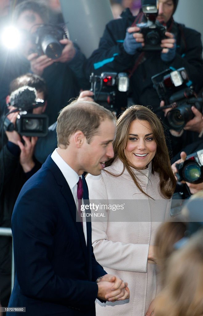 Britain's Prince William, Duke of Cambridge (L) and Britain's Catherine, Duchess of Cambridge (R) speak to dignitaries as photographers take pictures in the background ahead of a visit to Peterborough City Hospital in Peterborough, Cambridgeshire, north of London, on November 28, 2012. Britain's Prince William and his wife Catherine visited the university city that is home to their dukedom on November 28 for the first time since they were given their official titles. AFP PHOTO / LEON NEAL