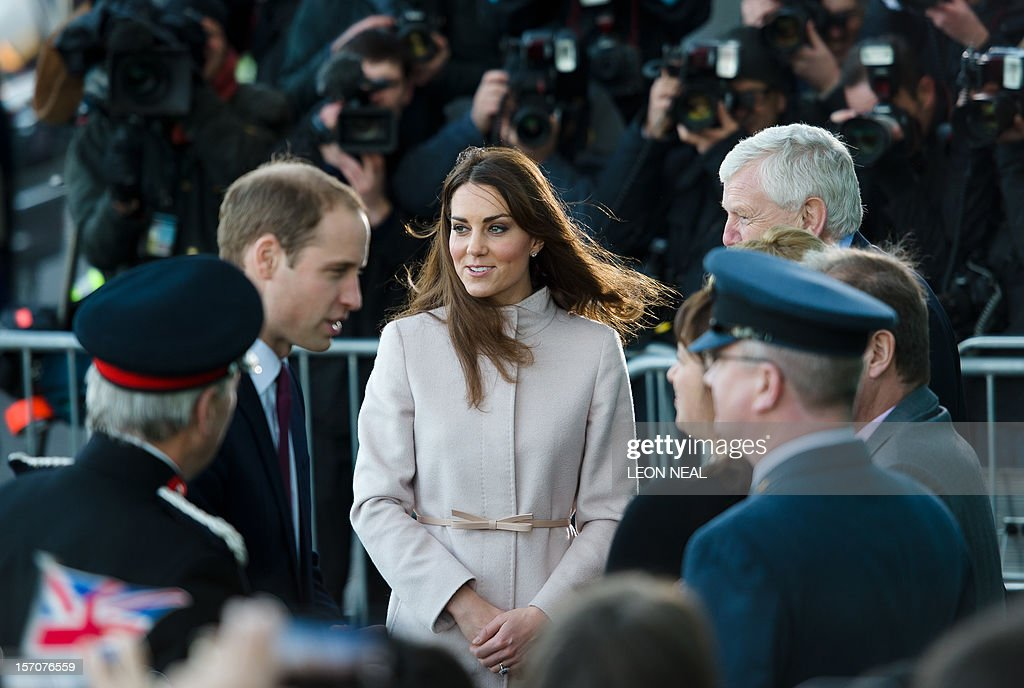 Britain's Prince William, Duke of Cambridge (L) and Britain's Catherine, Duchess of Cambridge (2L) speak to dignitaries as photographers take pictures in the background ahead of a visit to Peterborough City Hospital in Peterborough, Cambridgeshire, north of London, on November 28, 2012. Britain's Prince William and his wife Catherine visited the university city that is home to their dukedom on November 28 for the first time since they were given their official titles.