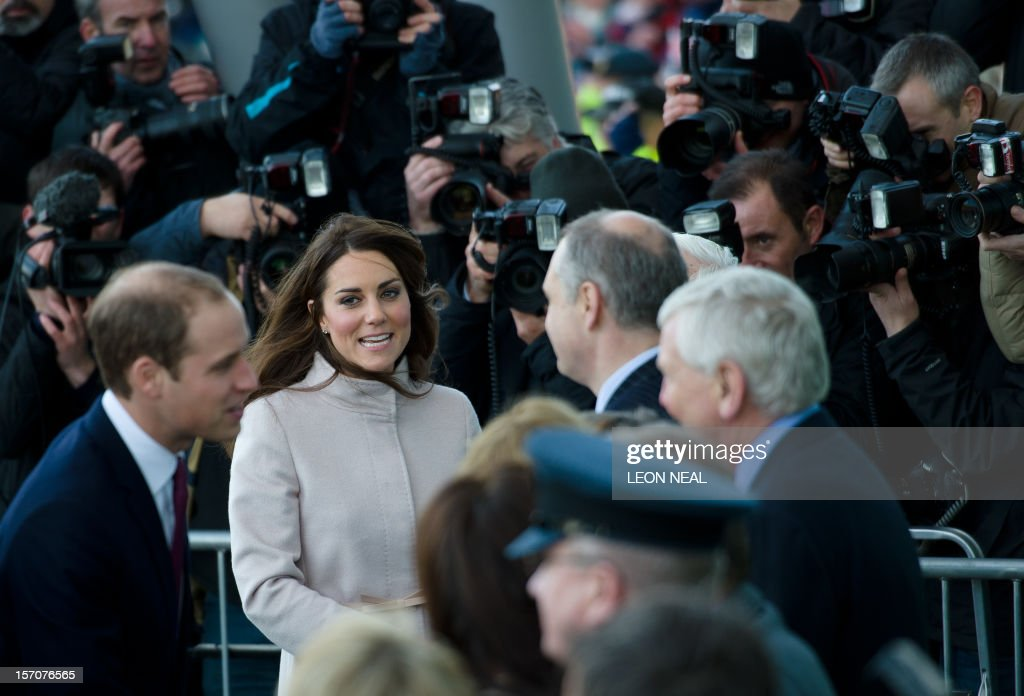 Britain's Prince William, Duke of Cambridge (L) and Britain's Catherine, Duchess of Cambridge (2L) speak to dignitaries as photographers take pictures in the background ahead of a visit to Peterborough City Hospital in Peterborough, Cambridgeshire, north of London, on November 28, 2012. Britain's Prince William and his wife Catherine visited the university city that is home to their dukedom on November 28 for the first time since they were given their official titles. AFP PHOTO / LEON NEAL