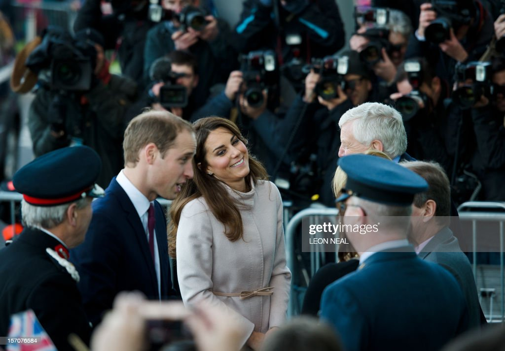 Britain's Prince William, Duke of Cambridge (L) and Britain's Catherine, Duchess of Cambridge (R) speak to dignitaries as they arrive visit Peterborough City Hospital in Peterborough, Cambridgeshire, north of London, on November 28, 2012. Britain's Prince William and his wife Catherine visited the university city that is home to their dukedom on November 28 for the first time since they were given their official titles. AFP PHOTO / LEON NEAL