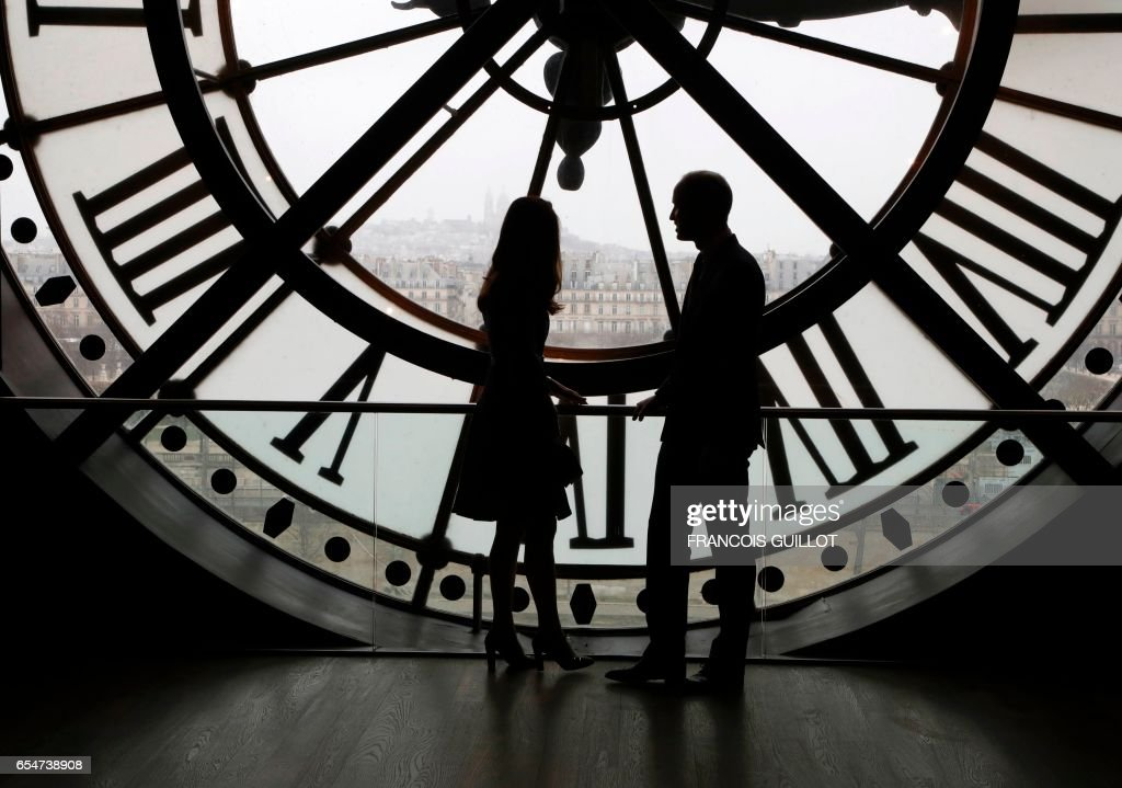 TOPSHOT - Britain's Prince William, Duke of Cambridge, and his wife Britain's Kate, Duchess of Cambridge, look across the River Seine at a view of Paris through the clock face at the Musee dOrsay - the former Gare d'Orsay train station- during their visit to the museum on March 18, 2017 on the second day of their two-day visit to the French capital. It is the prince's first official visit to the French capital since his mother Diana died there in a car crash in 1997. /