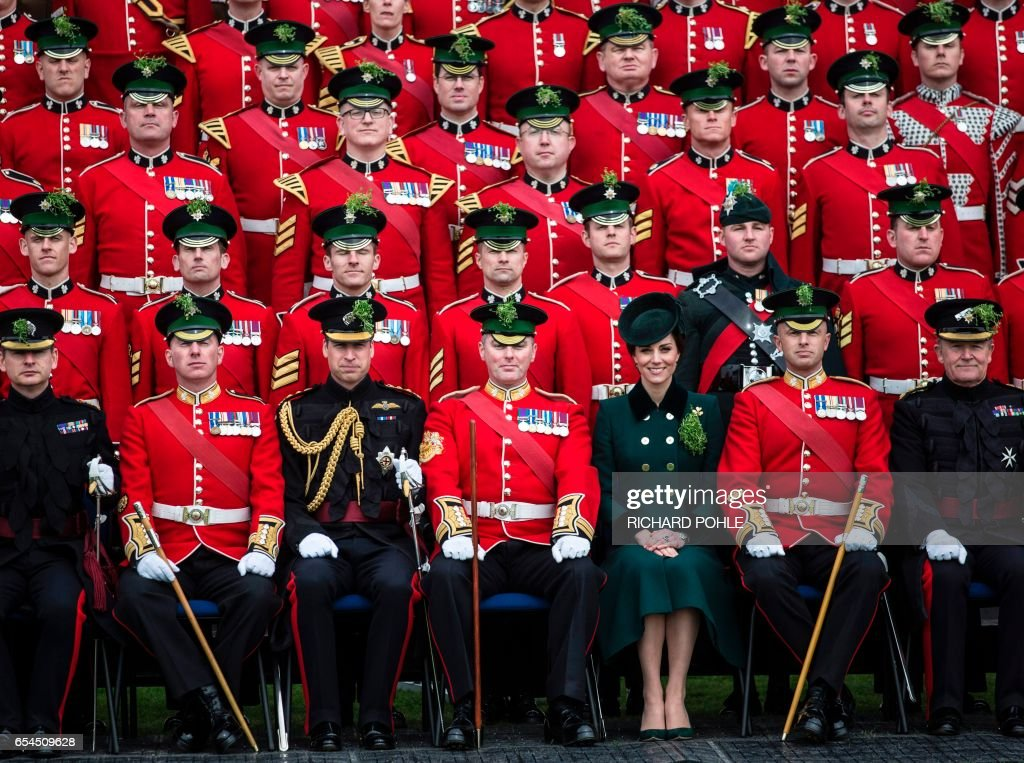 Britain's Prince William, Duke of Cambridge, (front row 3L) and his wife Britain's Catherine, Duchess of Cambridge (front row 3R) pose for a photograph with rmembers of the 1st Battalion Irish Guards, during their annual St Patrick's Day parade at Cavalry Barracks in Hounslow, west London on March 17, 2017. /