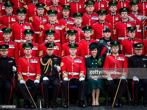 Britain's Prince William Duke of Cambridge and his wife Britain's Catherine Duchess of Cambridge pose for a photograph with rmembers of the 1st...