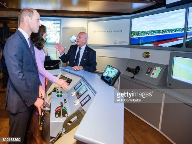 Britain's Prince William Duke of Cambridge and his wife Kate the Duchess of Cambridge stand at the wheel of a shipping simulator as they visit the...