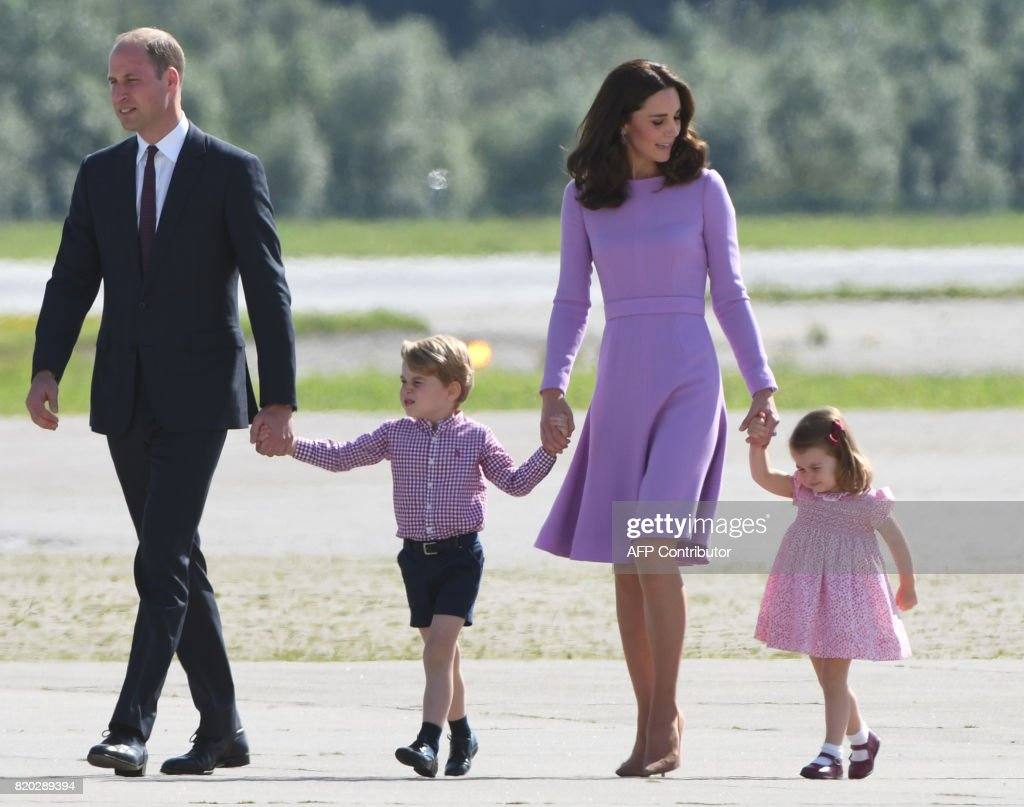 Britain's Prince William, Duke of Cambridge and his wife Kate, the Duchess of Cambridge, and their children Prince George and Princess Charlotte on the tarmac of the Airbus compound in Hamburg, northern Germany, on July 21,2017. The British royal couple are on the last stage of their three-day visit to Germany. / AFP PHOTO / Patrik STOLLARZ
