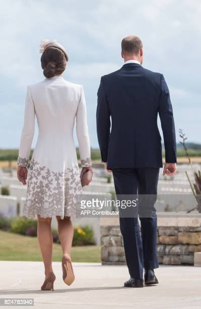 Britain's Prince William Duke of Cambridge and his wife Kate the Duchess of Cambridge walk during a visit to the Commonwealth War Graves Bedford...