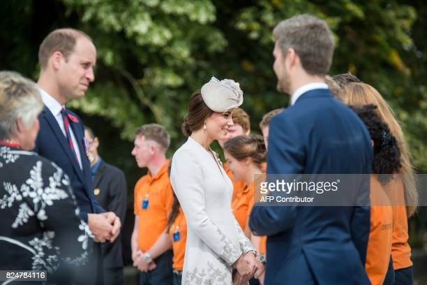 Britain's Prince William Duke of Cambridge and his wife Kate the Duchess of Cambridge speak with officials during a visit to the Commonwealth War...