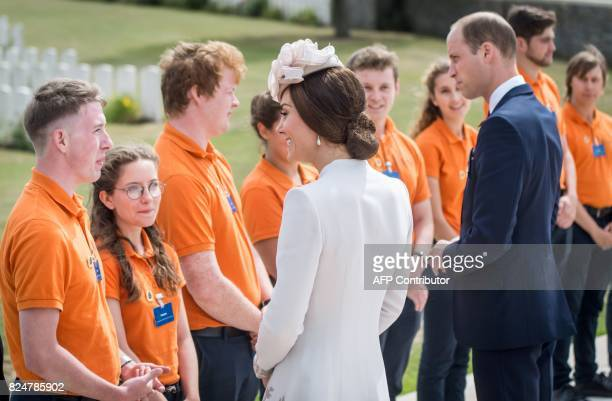 Britain's Prince William Duke of Cambridge and his wife Kate the Duchess of Cambridge speak with children during a visit to the Commonwealth War...