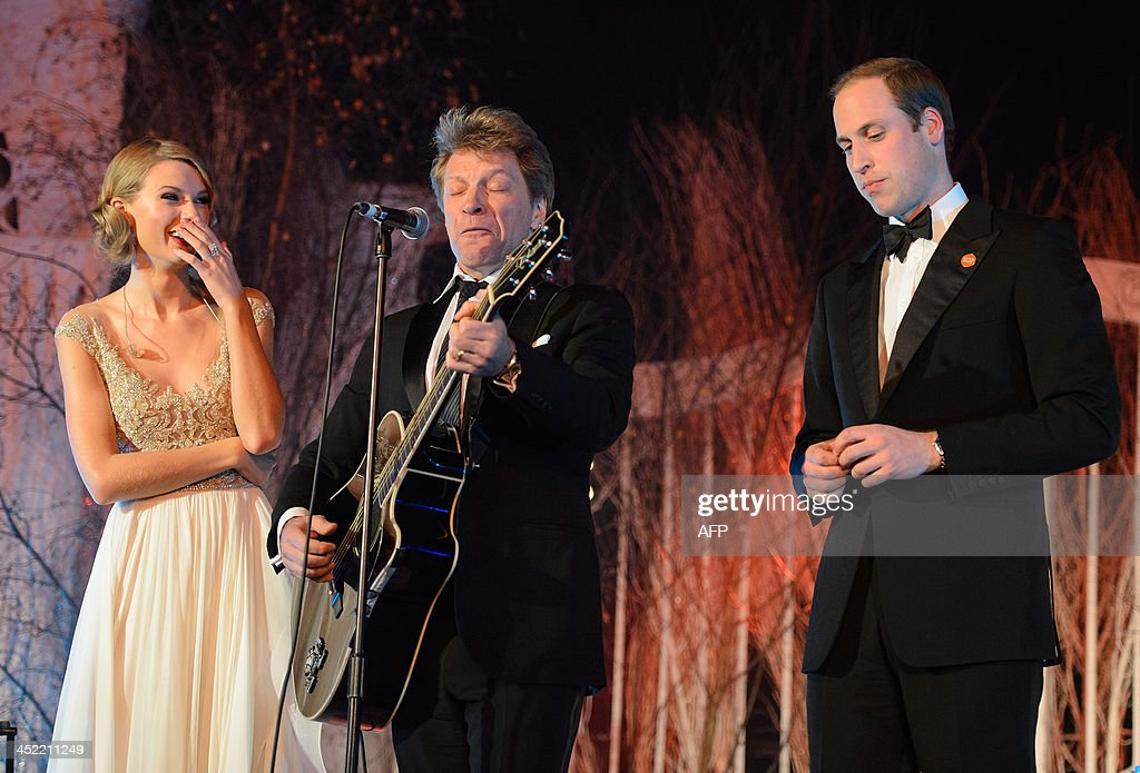 Britain's Prince William, Duke of Cambridge, (R) and US singer Taylor Swift (L) listen as US singer Jon Bon Jovi (C) plays a guitar solo at the Centrepoint Gala Dinner at Kensington Palace in London, on November 26, 2013.