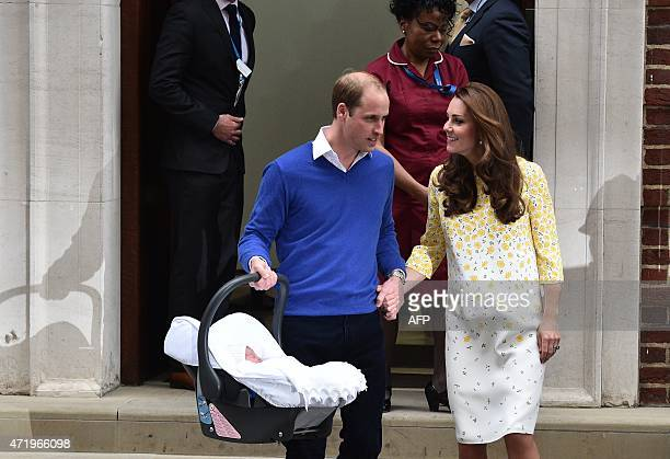 Britain's Prince William Duke of Cambridge carries his newlyborn daughter his second child in a car seat as he walks with his wife Catherine Duchess...