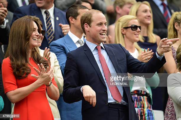 Britain's Prince William Duke of Cambridge gestures as he watches a member of the crowd catch Andy Murray's wristband from his seat in the royal box...