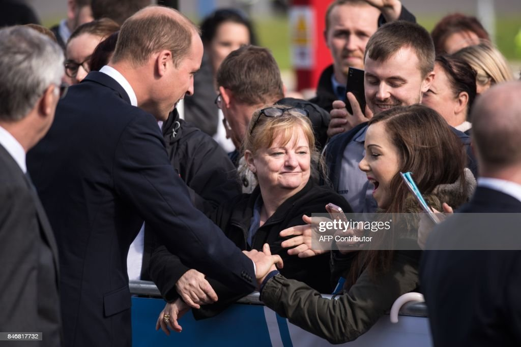 Britain's Prince William, Duke of Cambridge (L) greets well wishers before formally opening the new Urgent Care and Trauma Centre (UCAT) at Aintree University Hospital in Liverpool, north-west England on September 14, 2017. The newly redeveloped Trauma Centre includes the addition of a charity funded air ambulance helicopter landing pad. /
