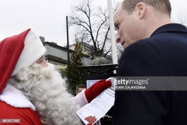Britain's Prince William Duke of Cambridge hands over a wish list by his son Prince George to a person dressed up as Santa Claus as he visits the...
