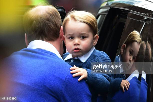 Britain's Prince William Duke of Cambridge helps his son Prince George of Cambridge out of a car as they return to the Lindo Wing at St Mary's...