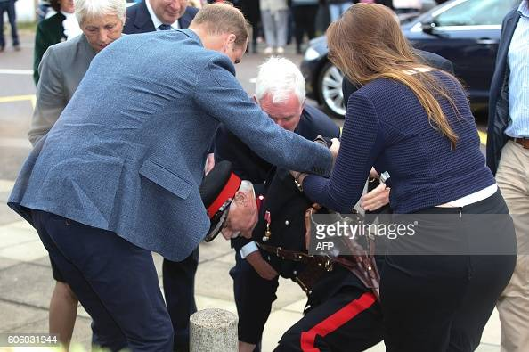 Britain's Prince William Duke of Cambridge helps Vice Lord Lieutenant of Essex Jonathan DouglasHughes to his feet after he fell over a bollard as the...