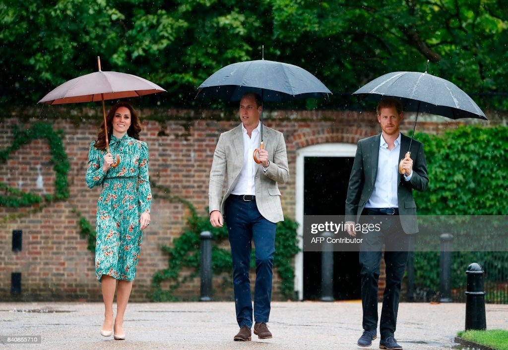 Britain's Prince William, Duke of Cambridge (C), his wife Britain's Catherine, Duchess of Cambridge (L) and his brother Britain's Prince Harry, shelter from the rain beneath umbrellas as they arrive to attend an event at the memorial gardens in Kensington Palace, west London on August 30, 2017. Princes William and Harry prepared to pay tribute to their late mother Princess Diana on Wednesday for the 20th anniversary of her death as wellwishers left candles and flowers outside the gates of her former London residence. The Princes visited the Sunken Garden in the grounds of Kensington Palace, which this year has been transformed into a White Garden, dedicated to their late mother, Britain's Diana, Princess of Wales. / AFP PHOTO / POOL / Kirsty Wigglesworth