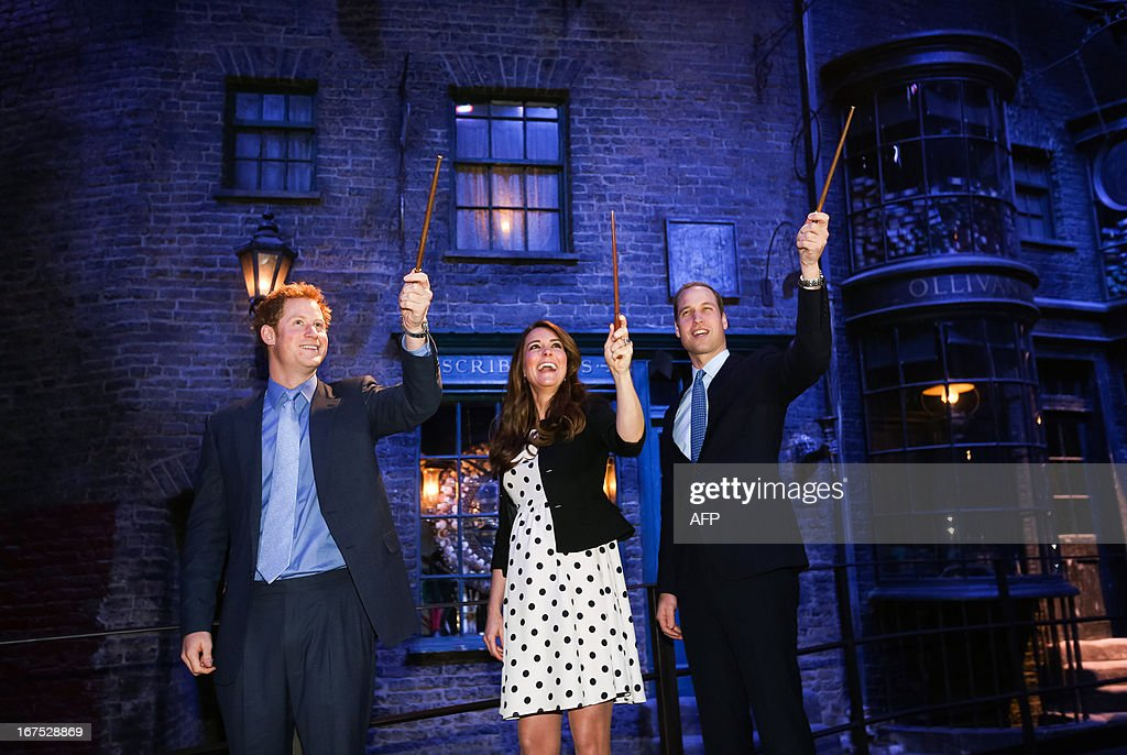 Britain's Prince William (R), Duke of Cambridge, his wife Catherine, Duchess of Cambridge, and brother Prince Harry raise their wands on the set used to depict Diagon Alley in the Harry Potter films during the Inauguration Of Warner Bros Studios in Leavesden, north London, on April 26, 2013.