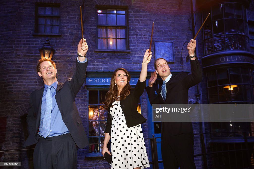 Britain's Prince William (R), Duke of Cambridge, his wife Catherine, Duchess of Cambridge, and brother Prince Harry raise their wands on the set used to depict Diagon Alley in the Harry Potter films during the Inauguration Of Warner Bros Studios in Leavesden, north London, on April 26, 2013. AFP PHOTO/POOL/PAUL ROGERS