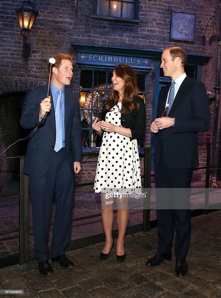 Britain's Prince William (R), Duke of Cambridge, his wife Catherine, Duchess of Cambridge, and brother Prince Harry share a joke as they hold wands on the set used to depict Diagon Alley in the Harry Potter films during the Inauguration Of Warner Bros Studios in Leavesden, north London, on April 26, 2013.