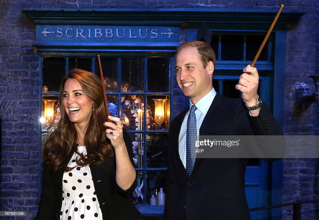 Britain's Prince William (R), Duke of Cambridge, his wife Catherine, Duchess of Cambridge, raise their wands on the set used to depict Diagon Alley in the Harry Potter films during the Inauguration Of Warner Bros Studios in Leavesden, north London, on April 26, 2013.