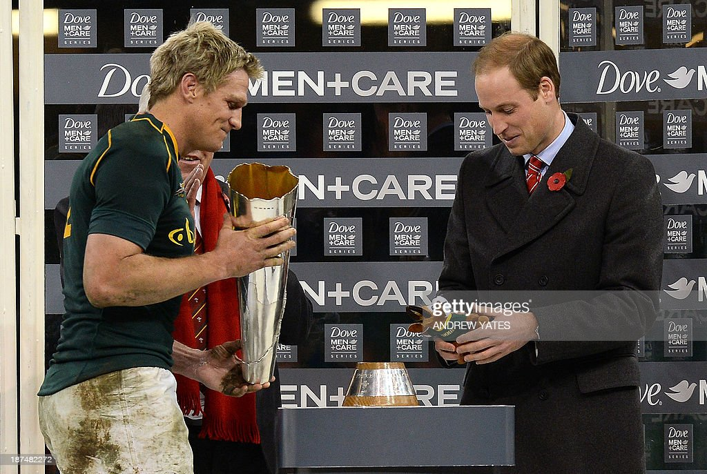 Britain's Prince William, Duke of Cambridge, is given a soft toy by South Africa's Jean de Villiers after presenting him the trophy at the end of the International rugby union test match between Wales and South Africa at the Millennium Stadium in Cardiff, south Wales, on November 9, 2013. South Africa won the match 24-15.