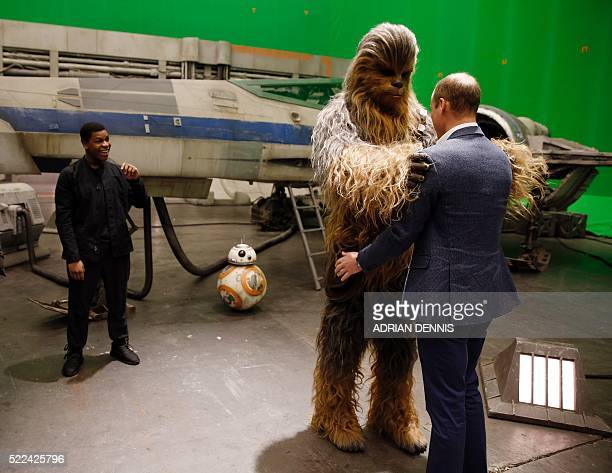 Britain's Prince William Duke of Cambridge is greeted by Chewbacca during a tour of the Star Wars sets at Pinewood studios in Iver Heath west of...