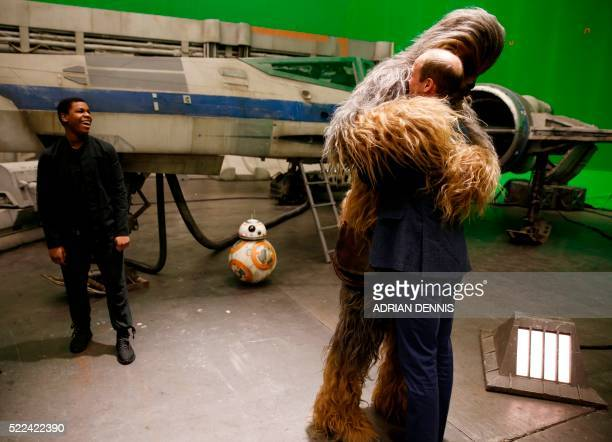 TOPSHOT Britain's Prince William Duke of Cambridge is hugged by Chewbacca as British actor John Boyega smiles during a tour of the Star Wars sets at...