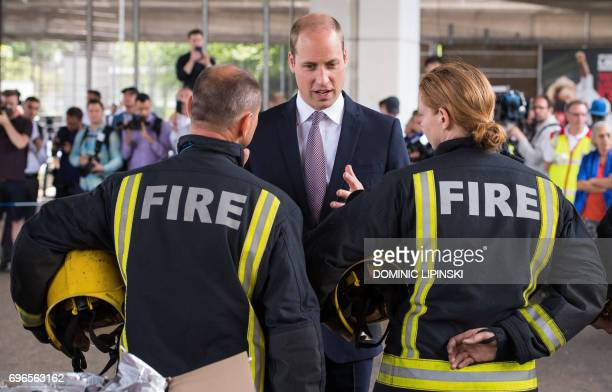 Britain's Prince William Duke of Cambridge meets firefighters during a visit to the Westway Sports Centre which is providing temporary shelter for...