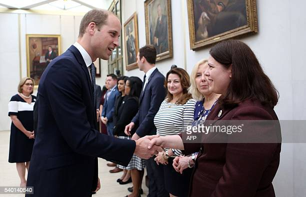 Britain's Prince William Duke of Cambridge meets staff after he and the Duchess of Cambridge signed a book of condolence for Orlando shooting victims...