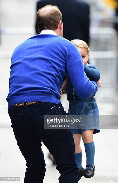 Britain's Prince William Duke of Cambridge picks up his son Prince George of Cambridge after he refused to walk from a car as they return to the...