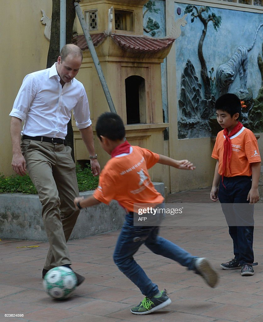 Britain's Prince William, Duke of Cambridge plays football with pupils as he visits a local primary school in the old quarters of Hanoi on November 16, 2016. Britain's Prince William is in Vietnam to attend an international conference on wildlife trafficking. / AFP / Nam HOANG