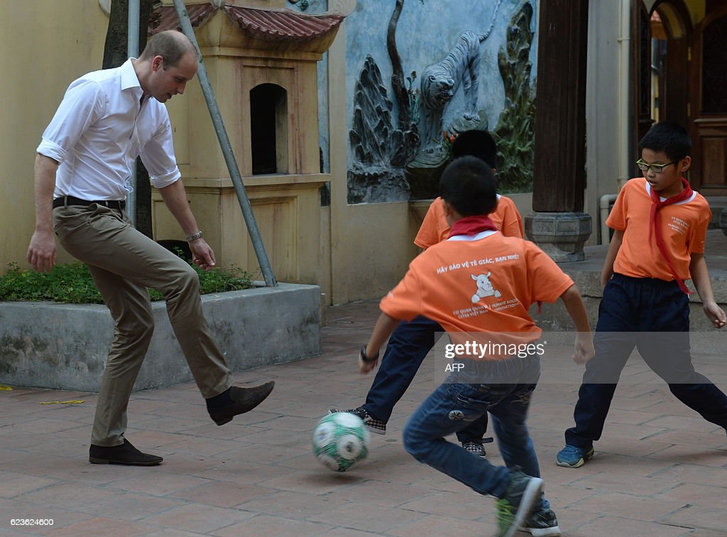 TOPSHOT - Britain's Prince William, Duke of Cambridge plays football with pupils as he visits a local primary school in the old quarters of Hanoi on November 16, 2016. Britain's Prince William is in Vietnam to attend an international conference on wildlife trafficking. / AFP / Nam HOANG