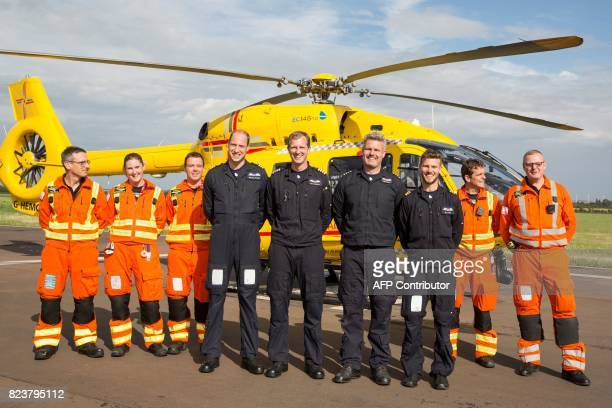 Britain's Prince William Duke of Cambridge poses for a photo with members of the day and night shift crews of the East Anglian Air Ambulance during...