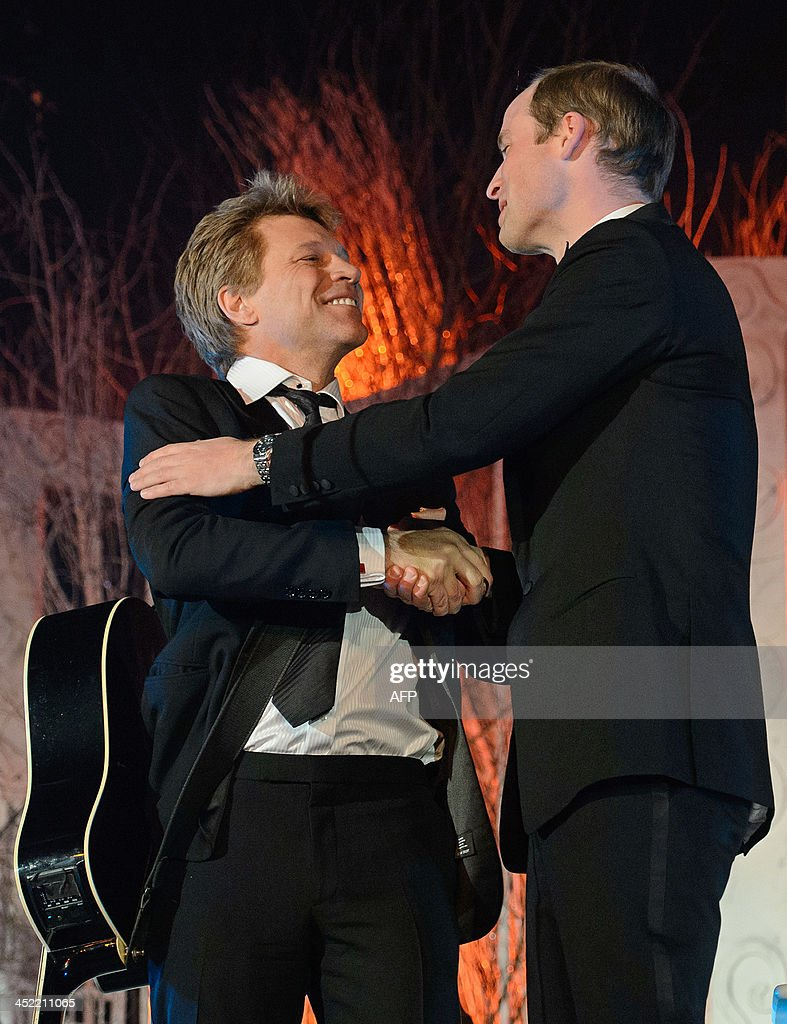 Britain's Prince William, Duke of Cambridge, (R) shakes hands with US singer Jon Bon Jovi after singing with him and US singer Taylor Swift (not pictured) at the Centrepoint Gala Dinner at Kensington Palace in London, on November 26, 2013.