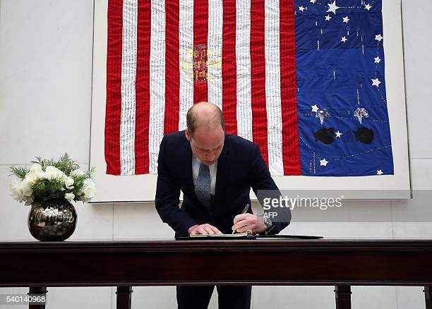 Britain's Prince William Duke of Cambridge signs a book of condolence for the Orlando shooting victims at the US Embassy in London on June 14 2016 US...