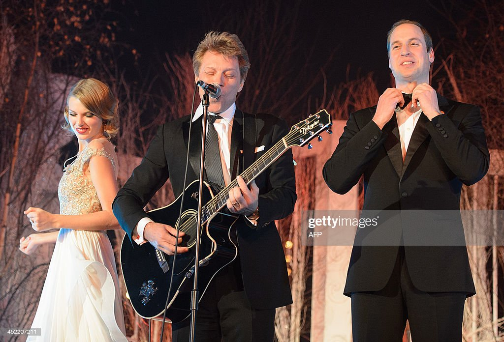 Britain's Prince William, Duke of Cambridge, (R) straightens his bow tie before singing with US musician's Taylor Swift (L) and Jon Bon Jovi (C) at the Centrepoint Gala Dinner at Kensington Palace in London, on November 26, 2013.