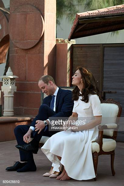 Britain's Prince William Duke of Cambridgeand his wife Catherine Duchess of Cambridge remove their shoes ahead of paying tribute during a visit to...