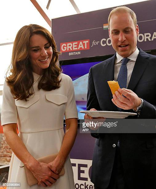 Britain's Prince William Duke of Cambridgeeats a 'Dosa' a traditional Indian food as his wife Catherine Duchess of Cambridge looks onduring a Young...