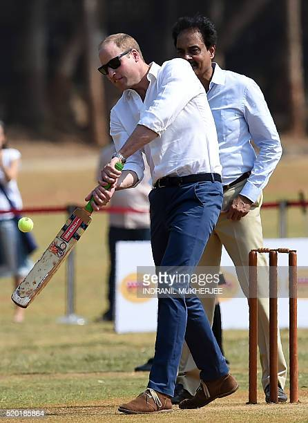 Britain's Prince William Duke of Cambridgeis watched by former Indian cricketer Dilip Vengsarkar as he and an unseen Catherine Duchess of Cambridge...