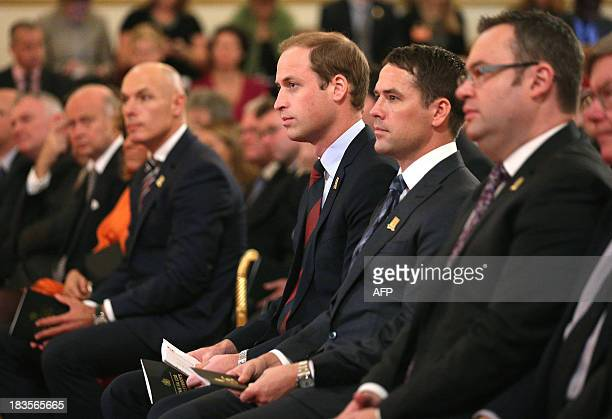 Britain's Prince William in his role as President of The Football Association sits with former England footballer Michael Owen in the Ballroom of...