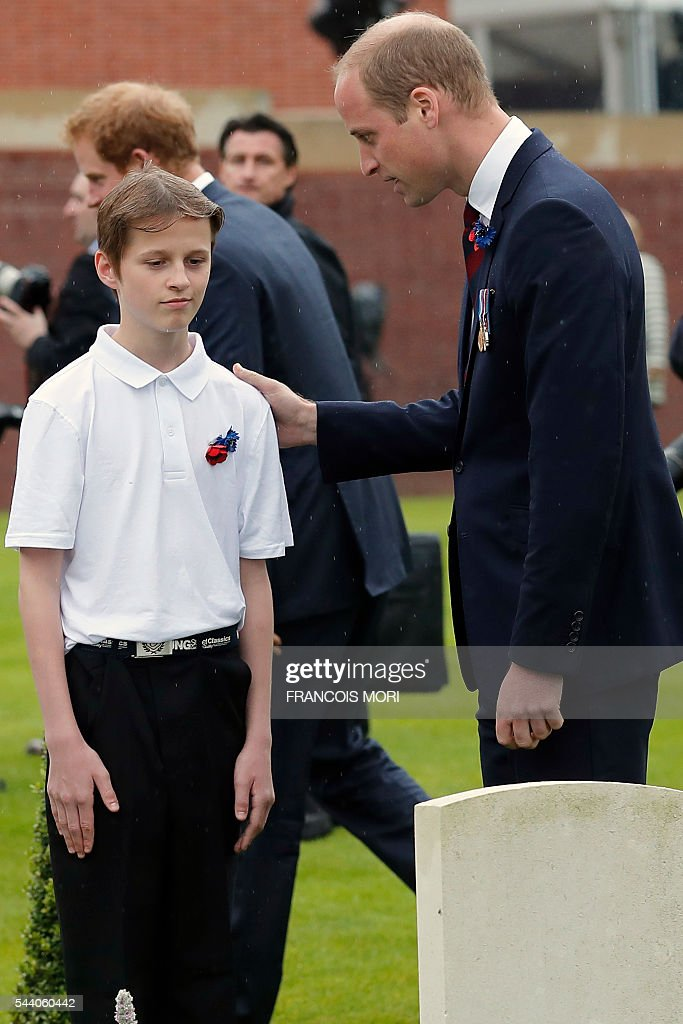 Britain's Prince William talks with a young volunteer in the cemetery of the Thiepval Memorial as he attends the memorial ceremony on July 1, 2016, in Thiepval, during which Britain and France will mark the 100 years since soldiers emerged from their trenches to begin one of the bloodiest battles of World War I (WWI) at the River Somme. Under grey skies, unlike the clear sunny day that saw the biggest slaughter in British military history a century ago, the commemoration kicked off at the deep Lochnagar crater, created by the blast of mines placed under German positions two minutes before the attack began at 7:30 am on July 1, 1916. / AFP / POOL / Francois Mori
