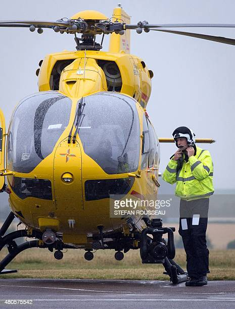 Britain's Prince William The Duke of Cambridge adjusts his helmet by an air ambulance as he begins his new job with the East Anglian Air Ambulance at...