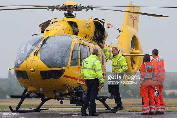 Britain's Prince William The Duke of Cambridge checks an air ambulance as he begins his new job with the East Anglian Air Ambulance at Cambridge...