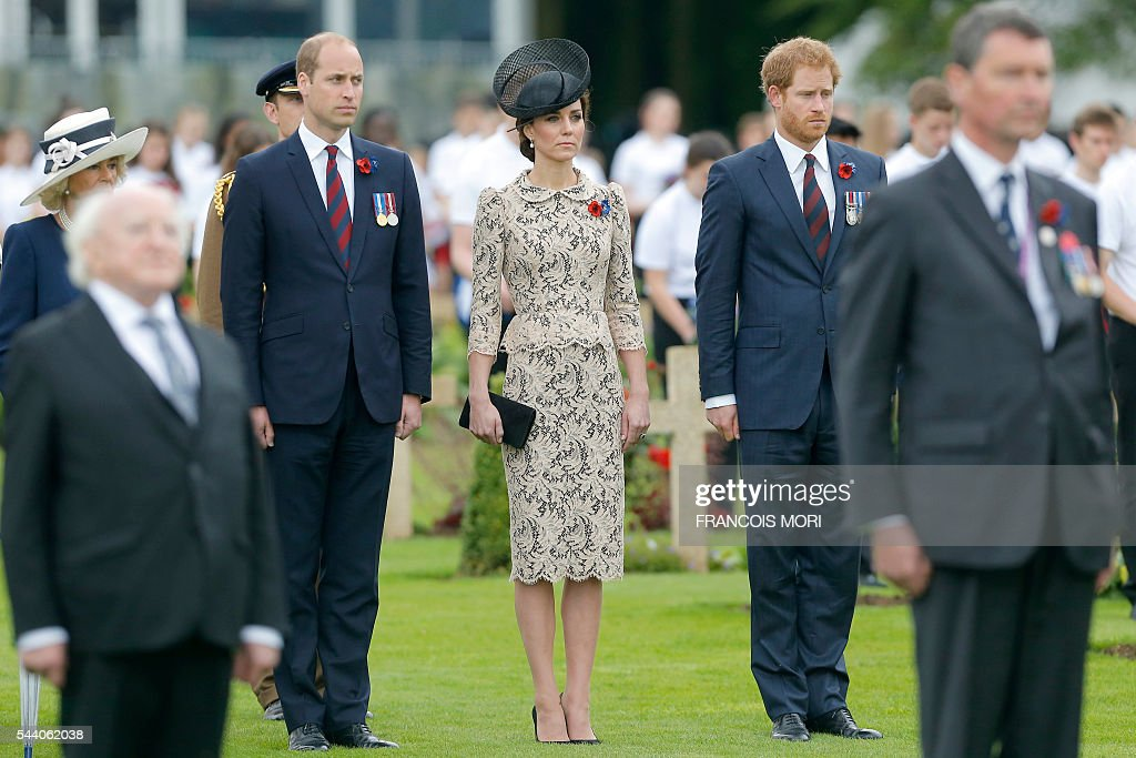 Britain's Prince William, the Duke of Cambridge, his wife Duchess Catherine of Cambridge, and Britain's Prince Harry stand guard to pay their respect as they attend the memorial ceremony on July 1, 2016, at the Thiepval Memorial in Thiepval, during which Britain and France will mark the 100 years since soldiers emerged from their trenches to begin one of the bloodiest battles of World War I (WWI) at the River Somme. Under grey skies, unlike the clear sunny day that saw the biggest slaughter in British military history a century ago, the commemoration kicked off at the deep Lochnagar crater, created by the blast of mines placed under German positions two minutes before the attack began at 7:30 am on July 1, 1916. / AFP / POOL / Francois Mori
