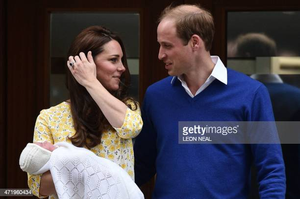 Britain's Prince William the Duke of Cambridge looks towards his wife Catherine the Duchess of Cambridge as they show their newlyborn daughter their...